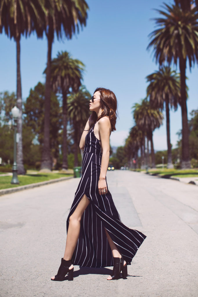 Jenny Tsang is wearing a black and white pinstripe Faithfull The Brand maxi dress with a high slit
