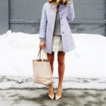 @laurenwells is wearing a lilac coat with a knitted ash grey sweater, paired with a creme handbag and heels