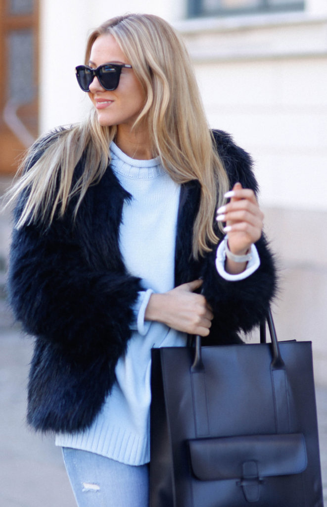 Street Style, March 2015: Jennifer Sandsjö is wearing a black faux fur jacket with a baby blue knitted sweater and a pair of light wash denim skinny jeans