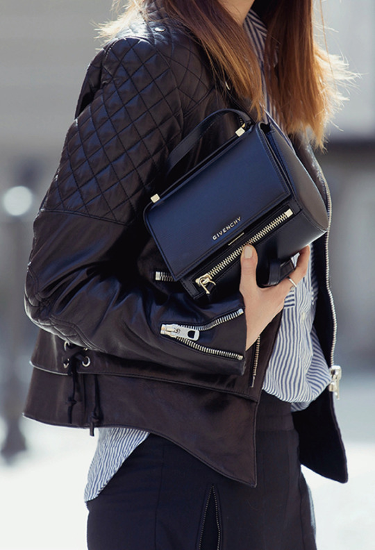 Just The Design: Nicoletta Reggio is wearing a Balenciaga black leather jacket with a Givenchy clutch and a Zara pinstripe shirt