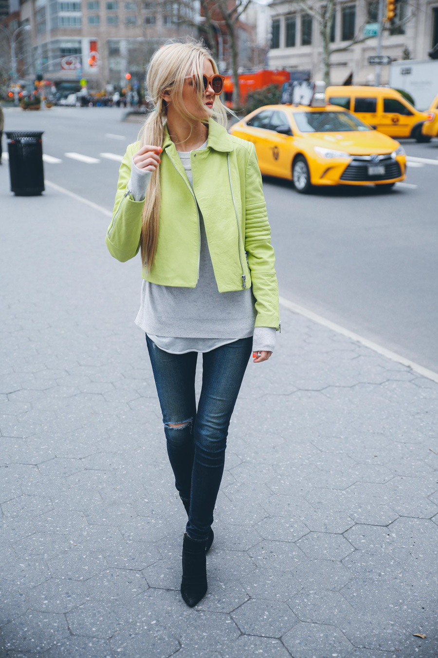Amber Fillerup Clark is wearing a lime green Aiah leather jacket with a grey Enza Costa sweater, ripped Rag & Bone jeans and black Carolinna Espinosa ankle boots