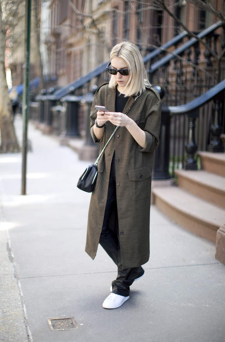 Lian Galliard is wearing an army green oversized Asos coat with leather River Island pants and Adidas sneakers