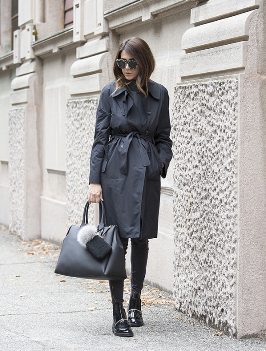 Nicoletta Reggio looks sleek and sophisticated in a black trench coat and slacks. Trench: Saint Laurent, Trousers: Zara, Boots: Asos, Sunglasses: ValleyEyewear.