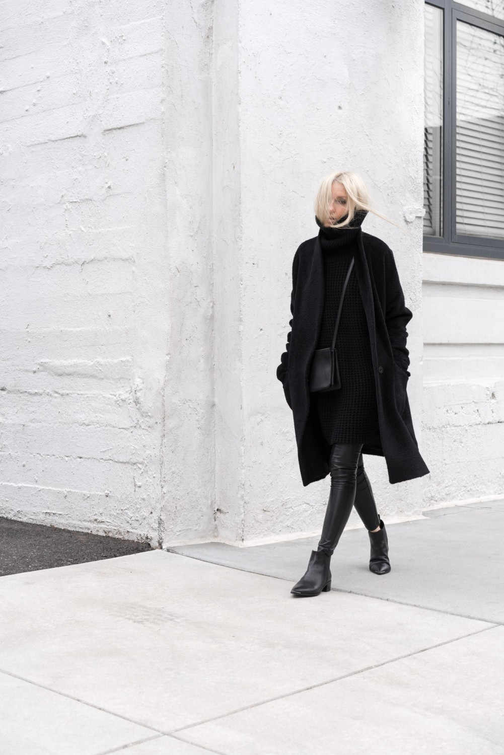 Figtny wears the all black trend in a sleek and sophisticated manner; creating cool, casual vibes with this turtleneck sweater dress and leather leggings combo. Coat: Eileen Fiser, Sweater: Hope Grand, Leggings: Aritzia, Boots: Acne, Bag: Celine.