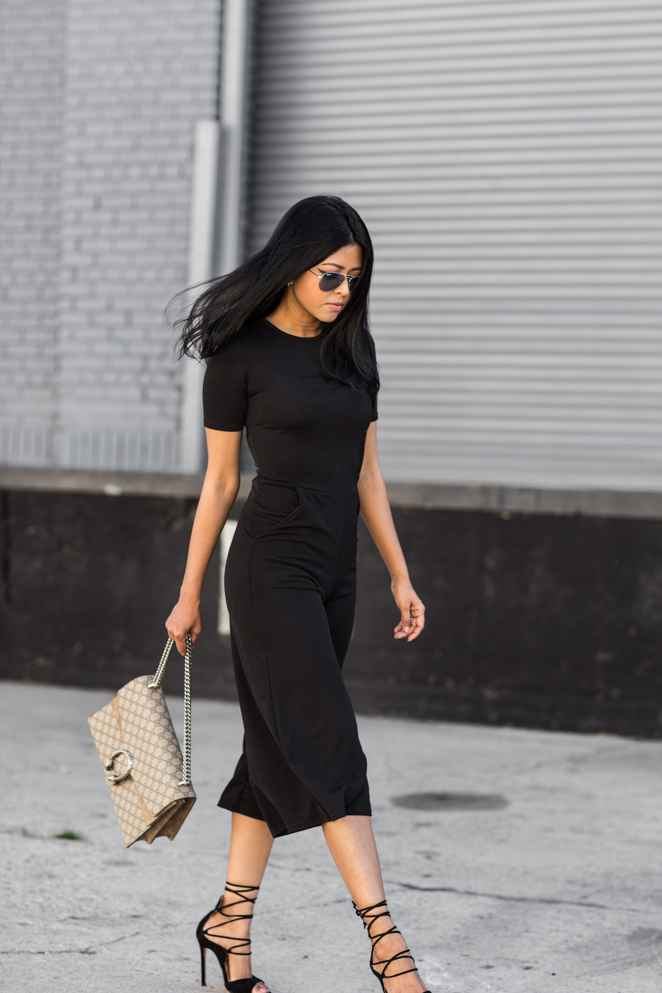 Sheryl Luke shows us how a simple black culotte jumpsuit is the perfect way to wear the all black trend! Simple and stylish, this jumpsuit - paired with strappy stilettos and a clutch - is to die for! Culotte Jumpsuit: Boohoo Petite, Coat: Boohoo Petite.