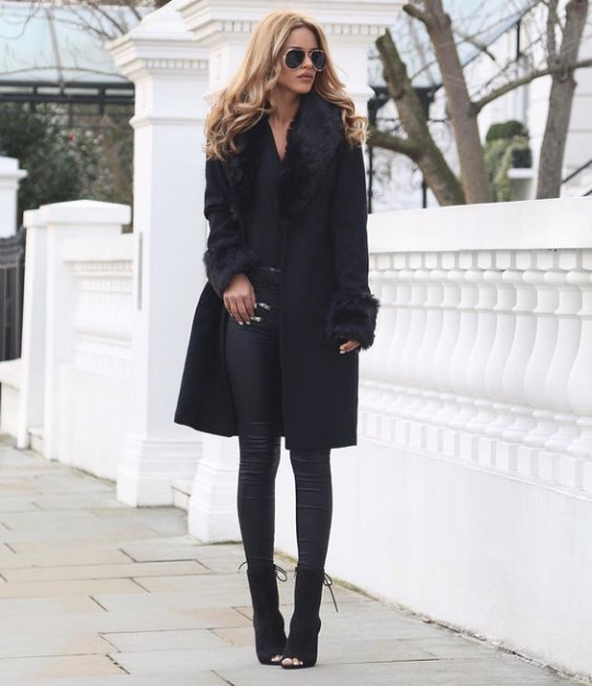 Nada Adelle is in head to toe all black here, wearing a glamorous outfit consisting of black leather leggings, a V neck tee, fur trimmed coat, and open toe heeled sandals. Outfit: Boohoo.