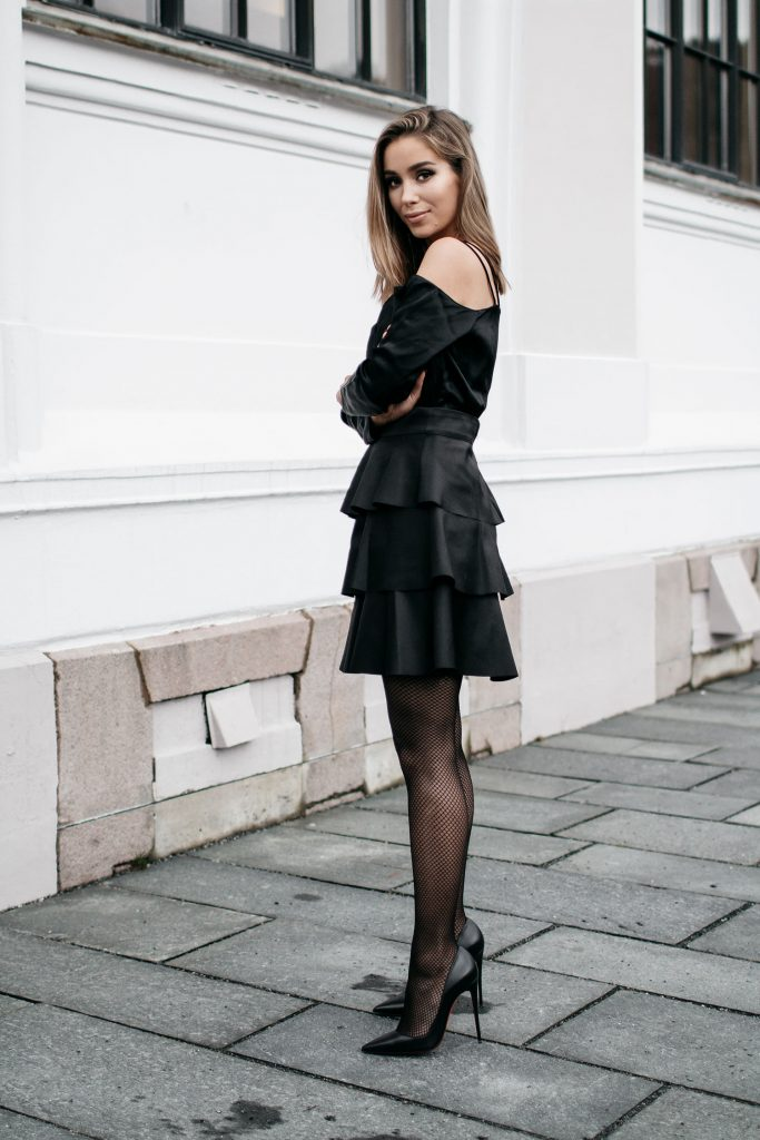 Emilie Tømmerberg shows us just how sleek all black can be, in this daring tiered off the shoulder dress, paired with fishnets and stilettos for a dark and sexy style.   Dress: Gina Tricot.