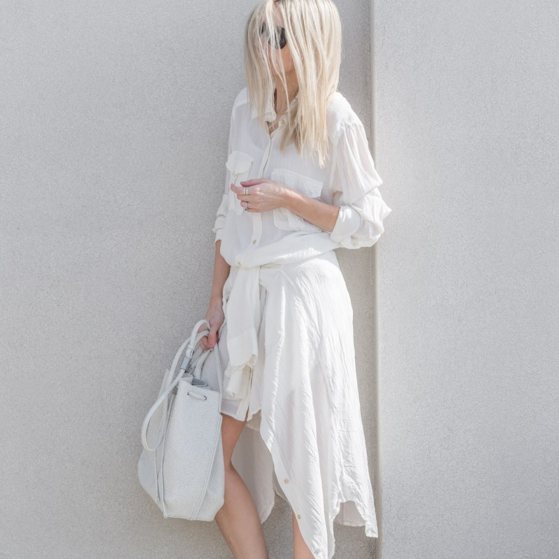 Figtny is wearing a white outfit, shirt dress and bucket bag both from Aritzia