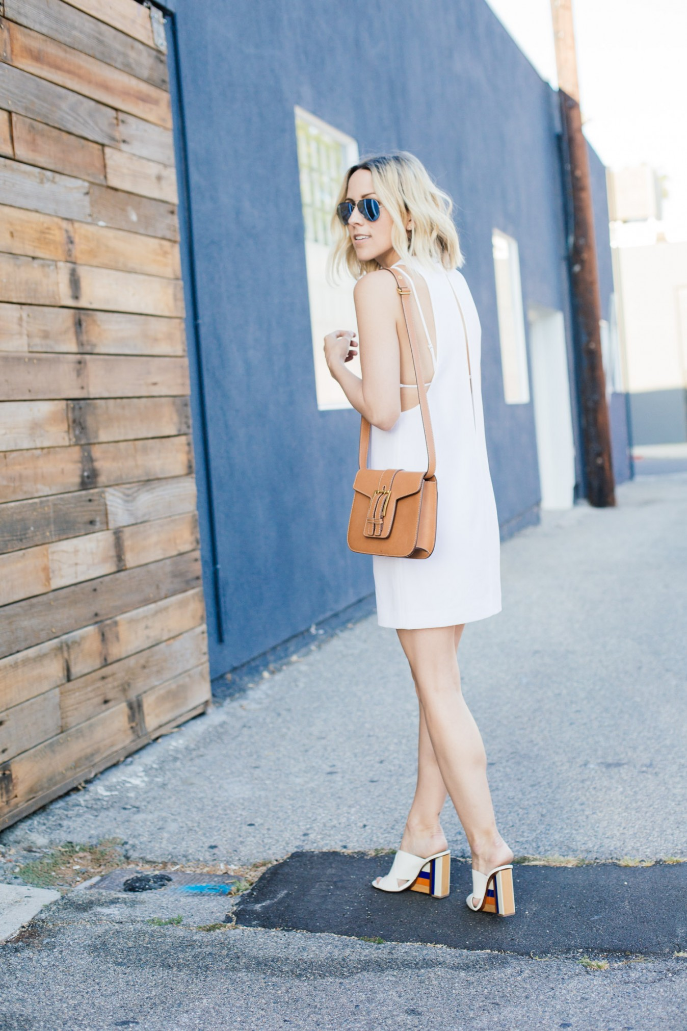 Jacey Duprie is wearing white mules with colour block from Tory Burch, white camisole dress from Alexander Wang, and the bag is from Yves Saint Laurent