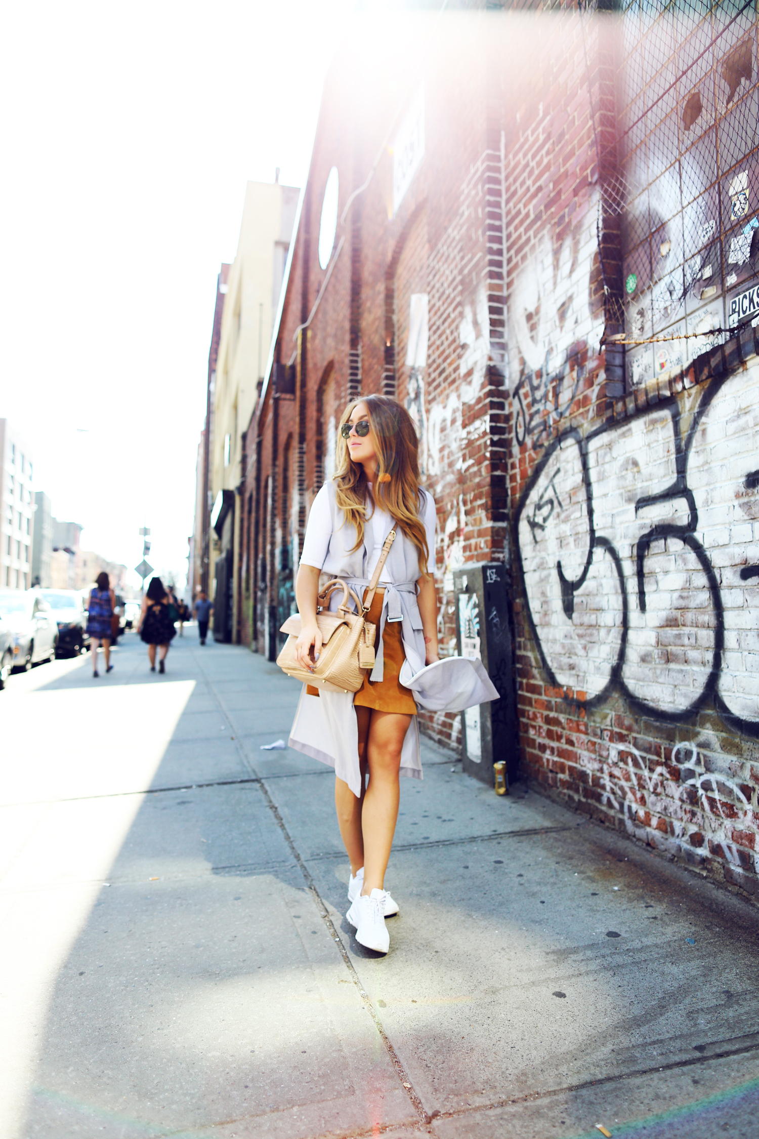 Via Just The Design: Angelica Blick is wearing a suede Zara mini skirt with a pale grey Topshop vest, a white Topshop tee, Nike sneakers and a beige leather handbag
