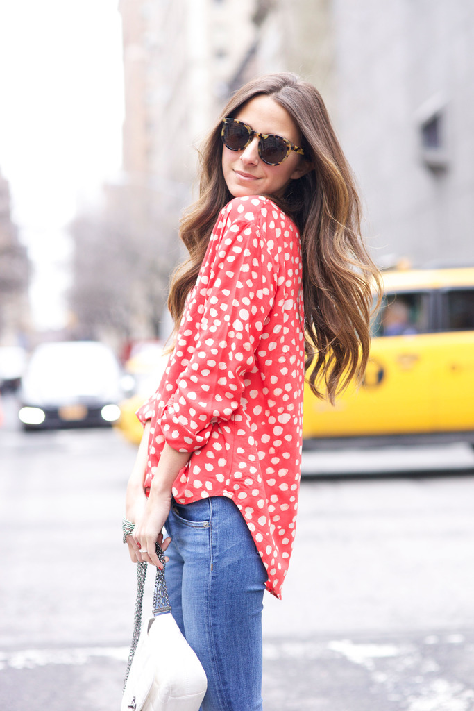 Arielle Nachami is wearing a red Graham & Spencer blouse paired with a pair of Rag & Bone jeans and Illesteva sunglasses