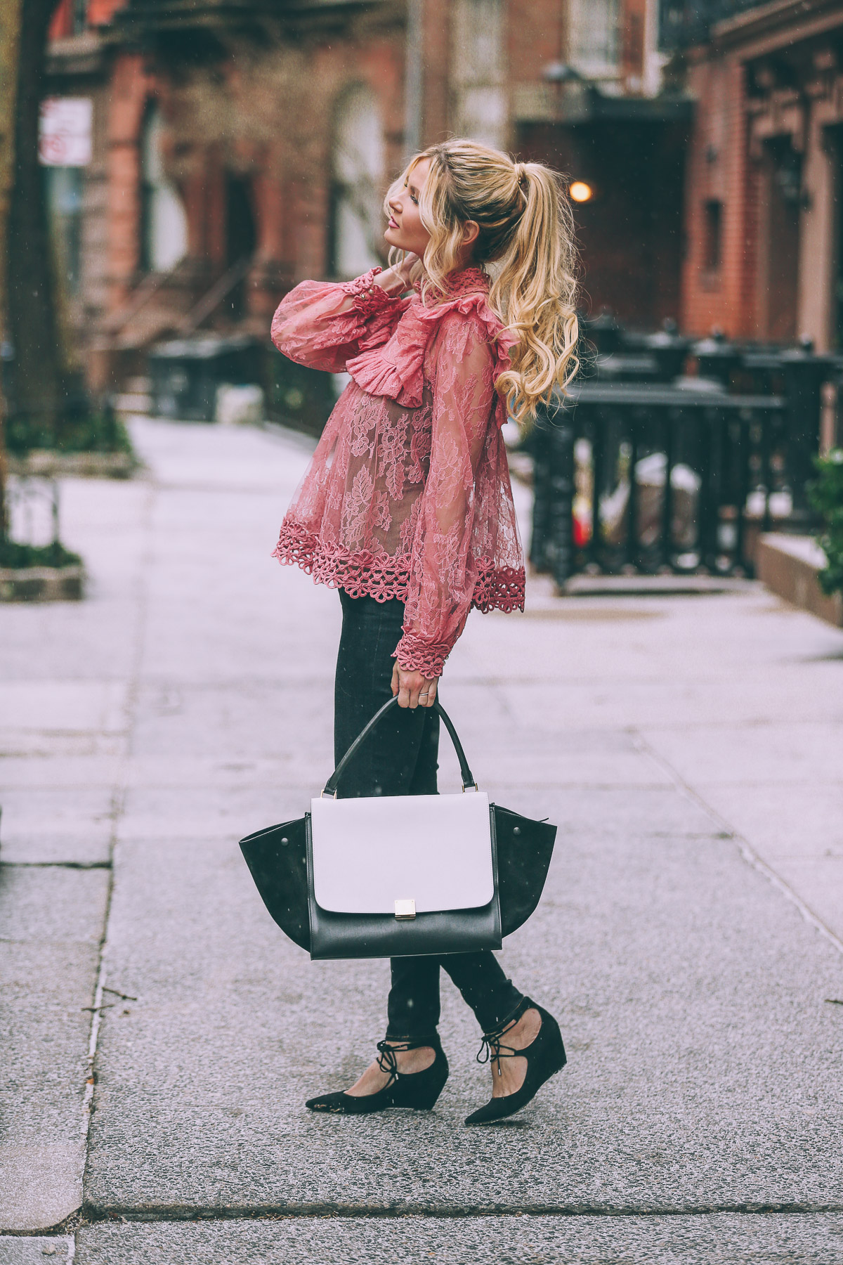 Amber Fillerup Clark is a vision in pink lace, sporting a gorgeous blouse from Zimmermann, paired with black jeans and a stylish asymmetrical monochrome bag. Blouse: Zimmermann, Jeans: J Brand, Shoes: Shopbop, Bag: Celine via Fashionphile.