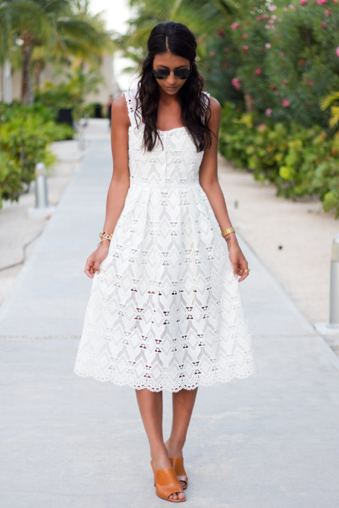 Kayla Seah is wearing a white Randy macramé lace dress from Maje, orange shoes from & Other Stories and the sunglasses are from Rayban