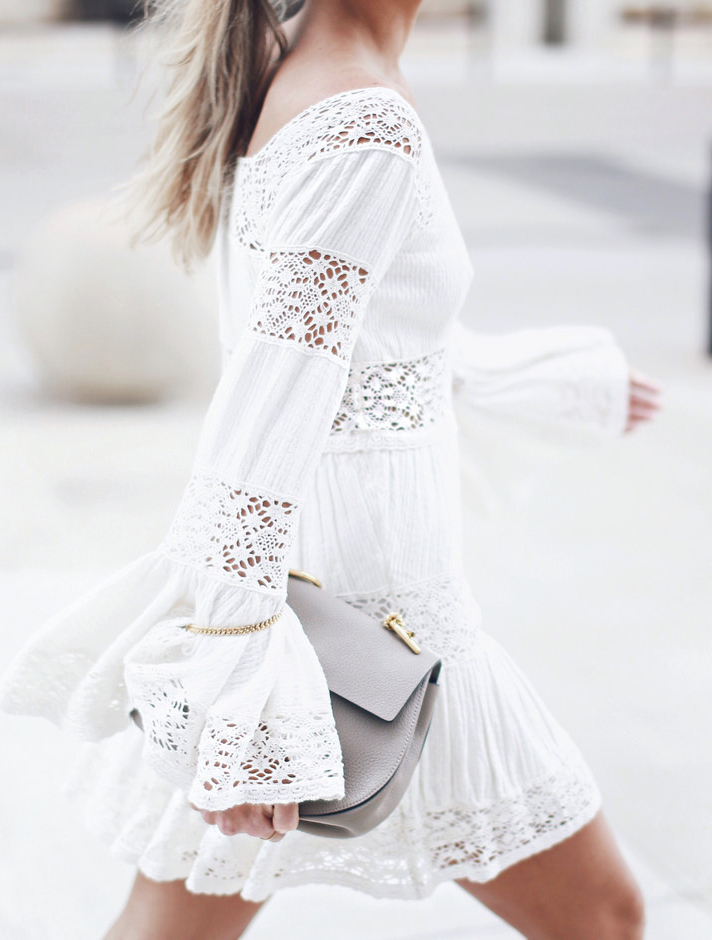 Mary Seng is wearing a white dress with insets of soft lace from Free People