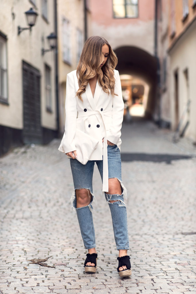 Lisa Olsson is wearing a white Zara blazer with a pair of Chicy distressed jeans