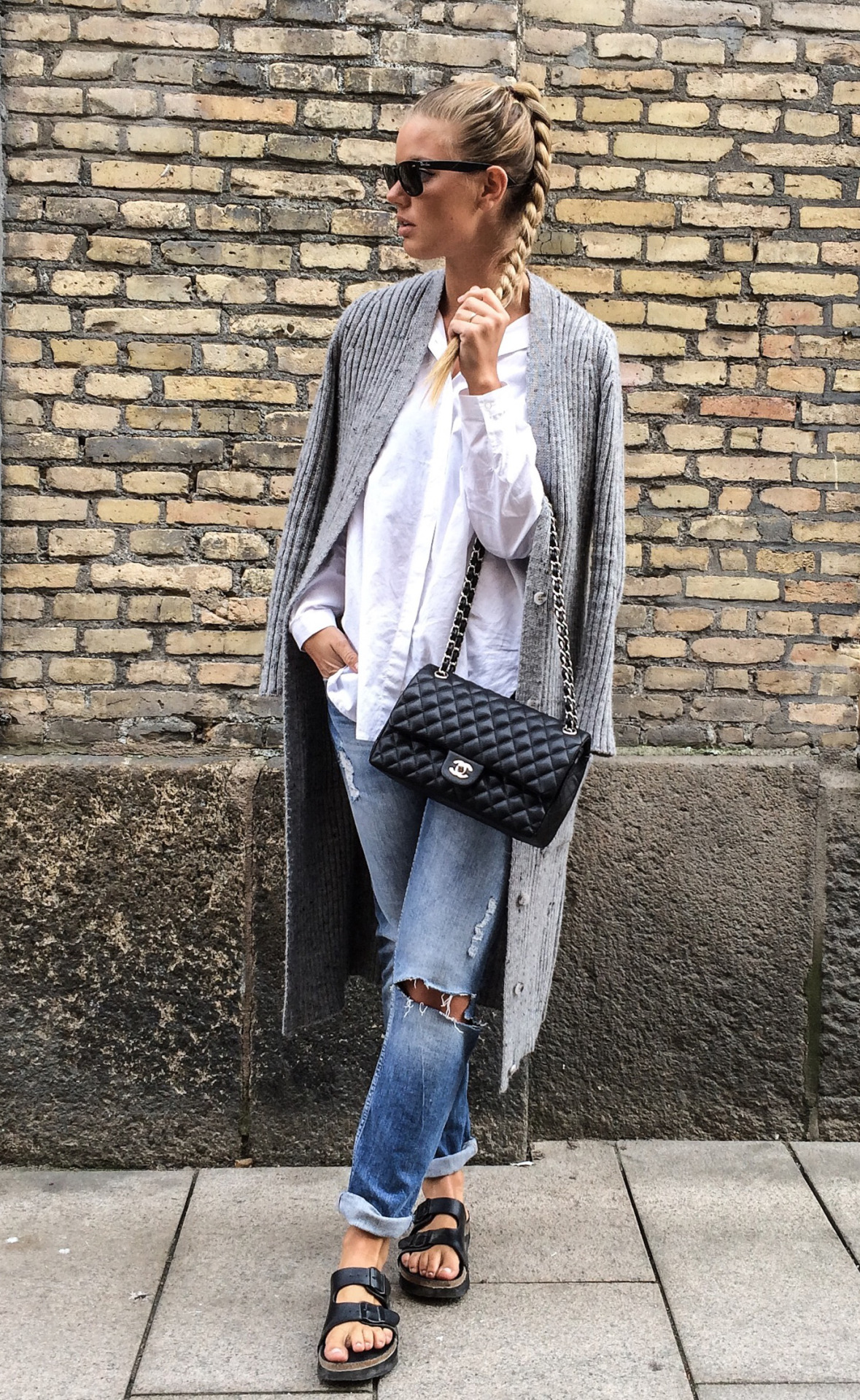 Frida Grahn is wearing a white shirt and distressed boyfriend jeans from Ginatricot with an ash grey Chiquelle oversized cardigan, black Din Sko sandals and a Chanel handbag