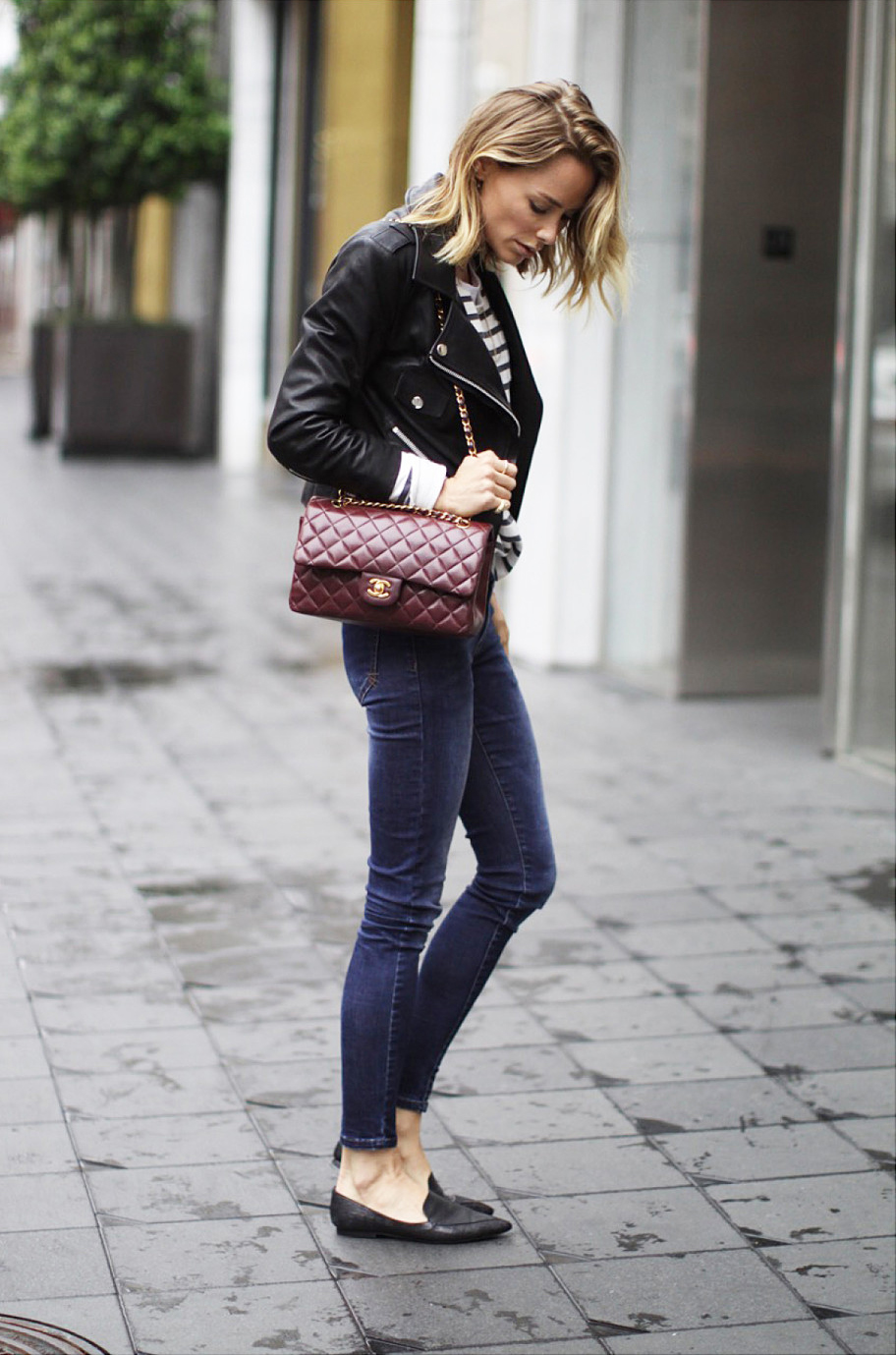 Anine Bing is wearing jeans, black cropped leather jacket, loafers and striped top from Anine Bing and the bag is vintage Chanel