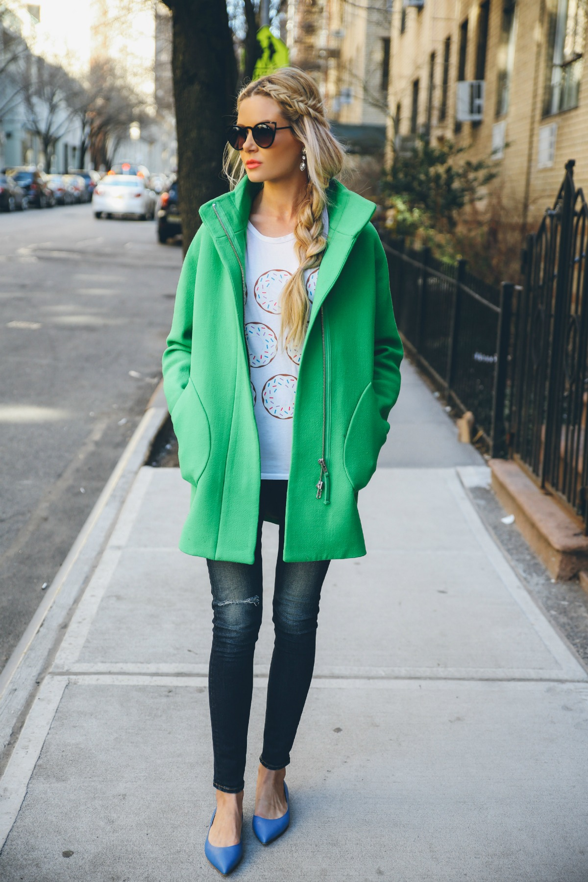 Amber Fillerup Clark is wearing a top from Ily Couture, green coat from J Crew, shoes from M Gemi and the sunglasses are from Quay
