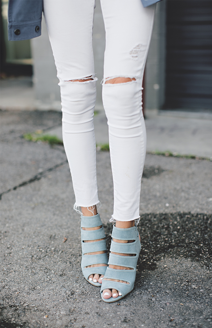 Christine Andrew is wearing a white jeans with ripped knees from TopShop and blue Play Along sandals from Seychelles
