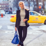 Janni Deler is wearing a black suit from Janni for Sanne and the white slip-on sneakers are from Nilson