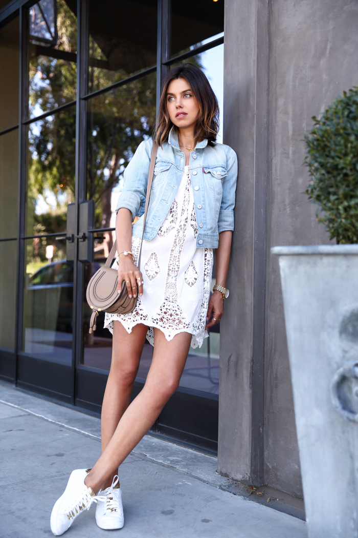 Street Style: Annabelle Fleur is wearing a cropped Levi denim jacket with a white lace Bridgette dress and leather Michael Kors sneakers