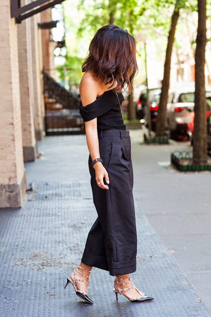 Krystal Bick in a black off the shoulder top, trousers and studded heels   Top: Reformation, Trousers: 3.1 Phillip Lim, Heels: Valentino
