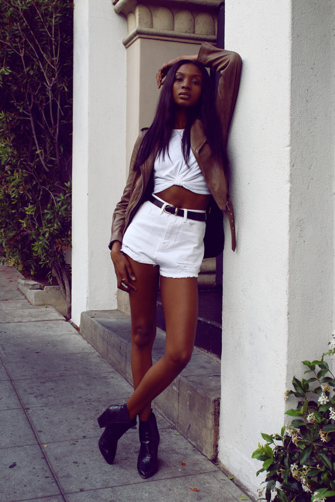 Street Style: Natasha Ndlovu is wearing a beige All Saints leather jacket, a white Missguided crop top and shorts with a pair of black Asos ankle boots