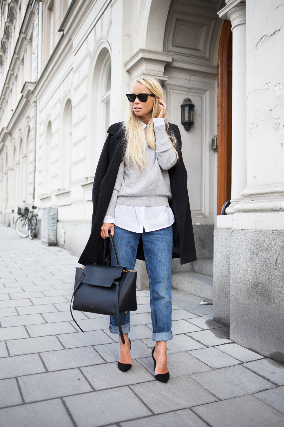 Via Just The Design: Lisa Olsson is wearing a black maxi coat from Asos with pale grey H&M sweater and light wash denim jeans