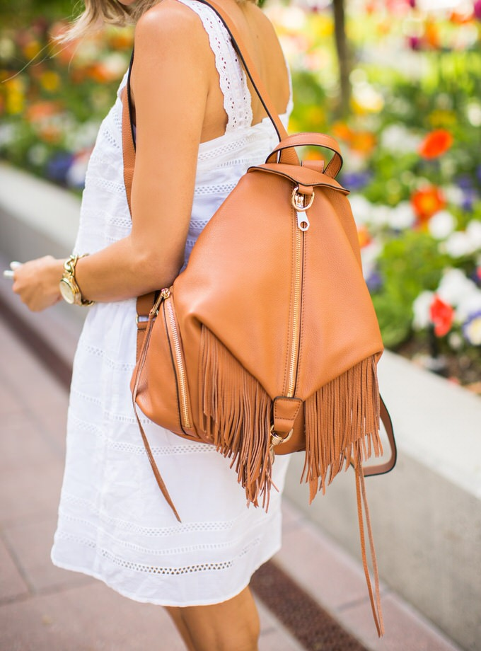 Via Just The Design: Christine Andrew is wearing a beige Rebecca Minkoff fringed backpack with a lace Topshop dress