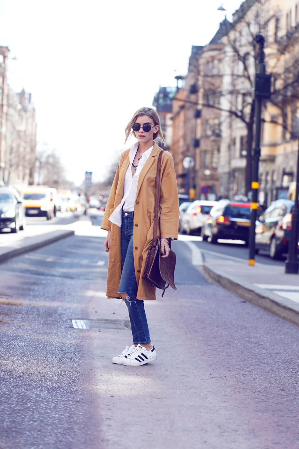 Elsa Ekman is wearing a beige Monki mac coat, distressed River Island jeans, a white Gant shirt and Adidas Superstar sneakers