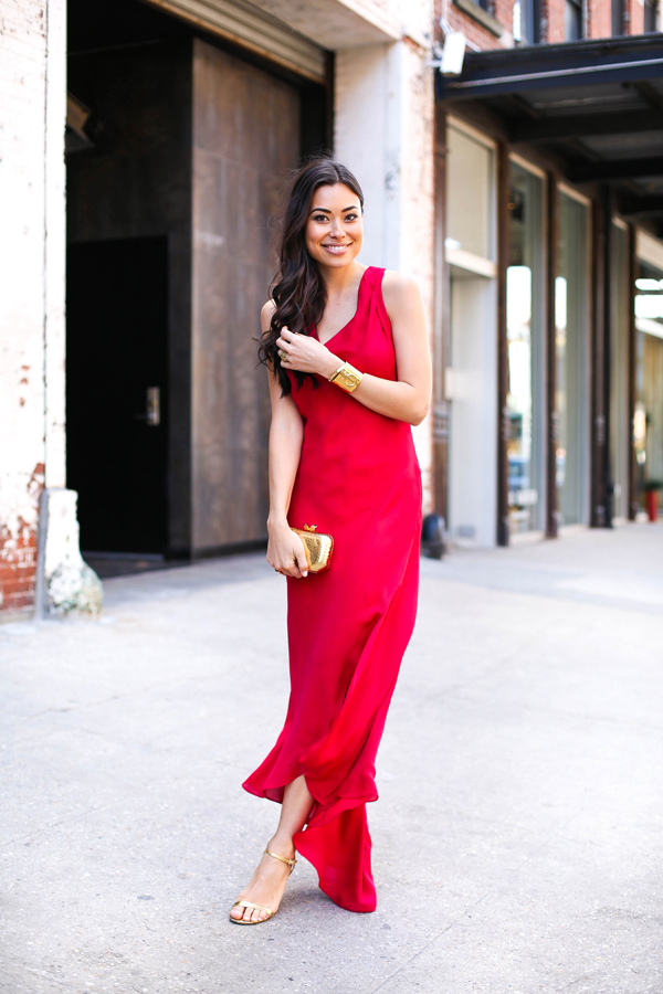 Kat Tanita is wearing a crimson red silk Haute maxi dress with a pair of golden Michael Kors heels