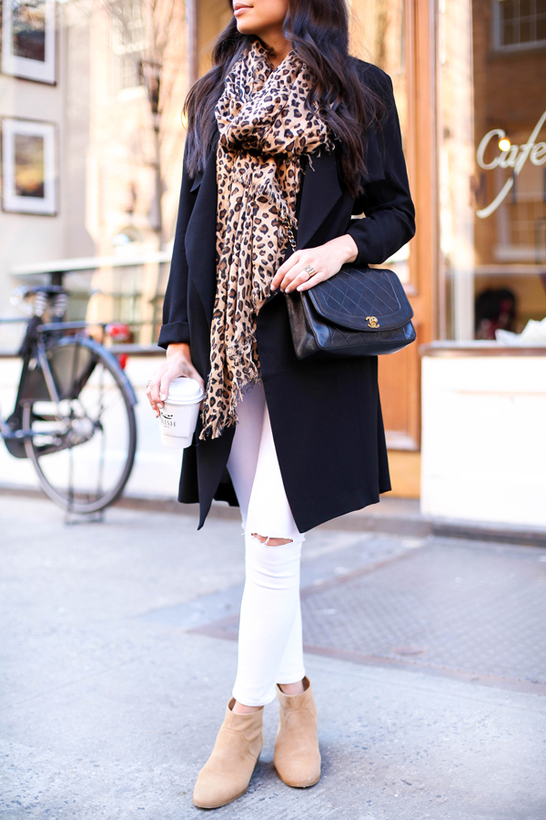 Kat Tanita is wearing a leopard print Sole Society scarf with a black Forever 21 coat, white Frame Denim skinny jeans and creme Sole Society ankle boots