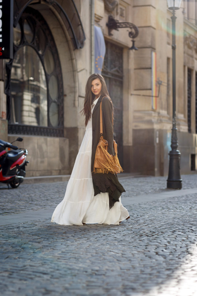 Larisa Costea is wearing a white bohemian style Sheinside maxi dress paired with a Free People trench coat and a Jadu fringed bag