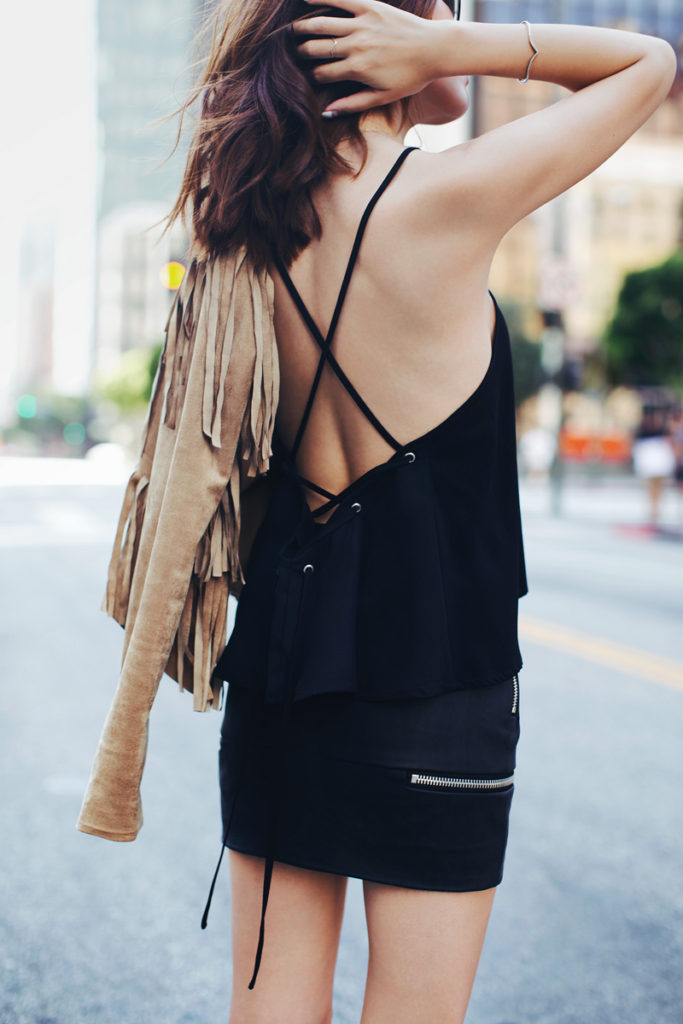 Street Style, April 2015: Jenny Tsang is wearing a suede camel Sam Edelman fringe jacket with a black Fifth Label crop top and a Nastygal mini skirt