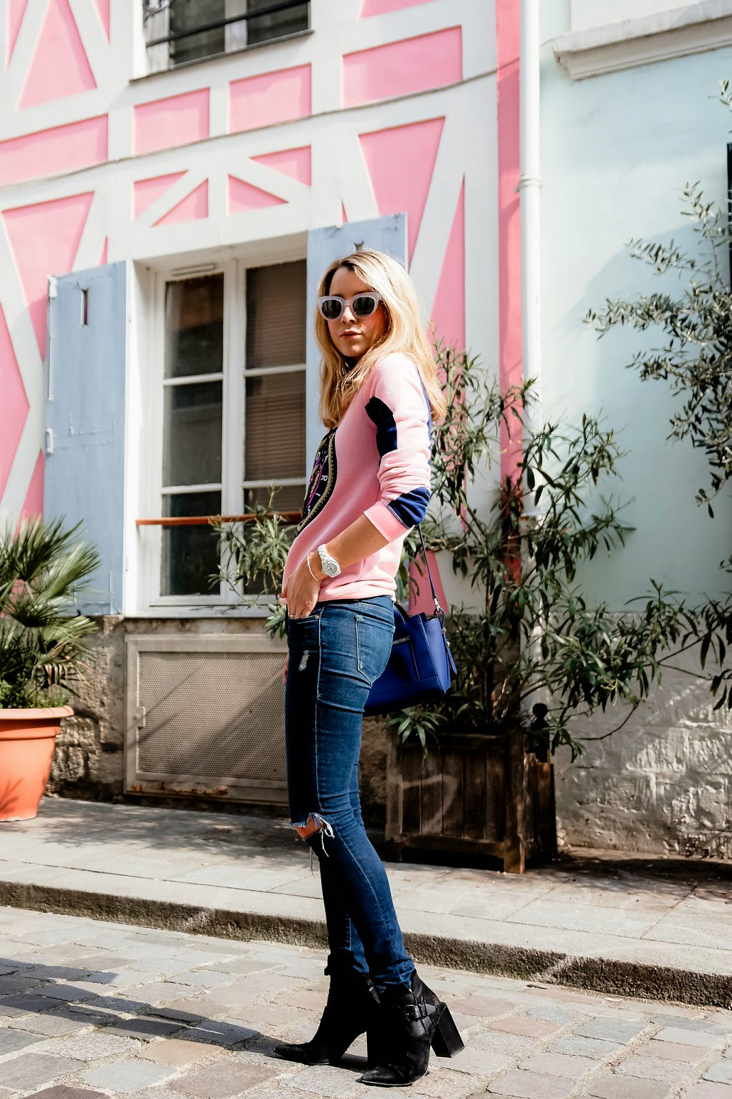 Street Style: Caroline Louis is wearing a candy pink sweater and royal blue side bag from Kenzo with Frame Denim jeans and black Senso ankle boots