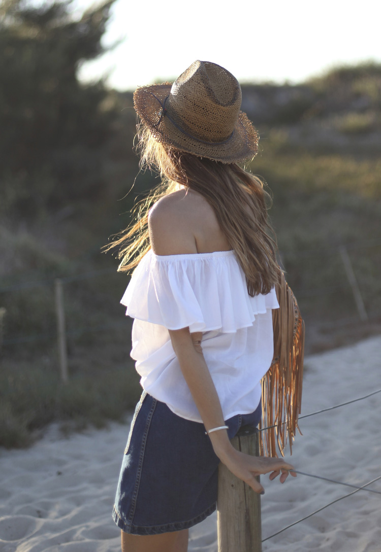Silvia Garcia in a dark wash denim skirt and off the shoulder white top with a beige fringed bag and beach hat Top: SuiteBlanco, Skirt: Zara, Hat: Parfois