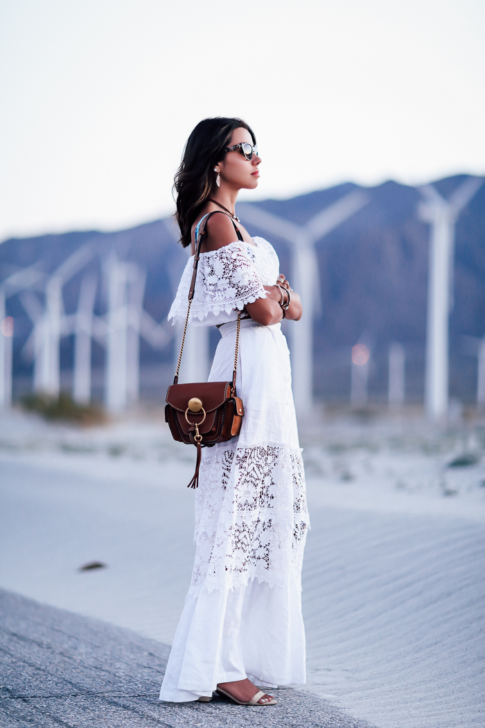 Annabelle Fleur is wearing perhaps the ultimate bohemian style here; a stunning lace-detailed off the shoulder maxi dress. This style is perfect for any summer evening, and will surely give you a style which any true bohemian would be jealous of! Dress: Miguelina Kimora.