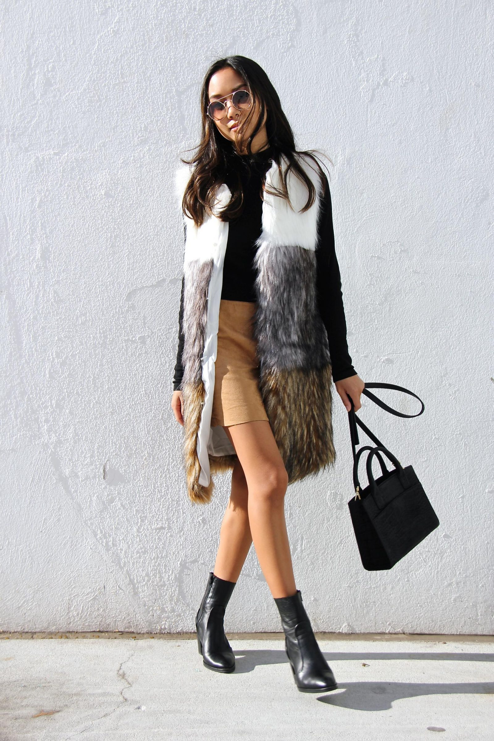 Faux fur is a must have if you are invested in attaining a true bohemian style! Linh Niller Huynh is rocking the hippie vibe in this gorgeous neutral coloured faux fur vest, paired with ankle boots and a beige mini skirt. Top/ Dress: H&M, Fur Vest: Missguided, Shoes: Topshop, Bag: Emily Cho.