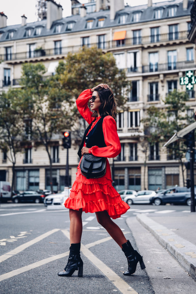 Annabelle Fleur goes all out bohemian in a red silk-satin dress with a tiered skirt and a little black waistcoat.   Dress: Paul & Joe, Bag/Boots: Chloe.