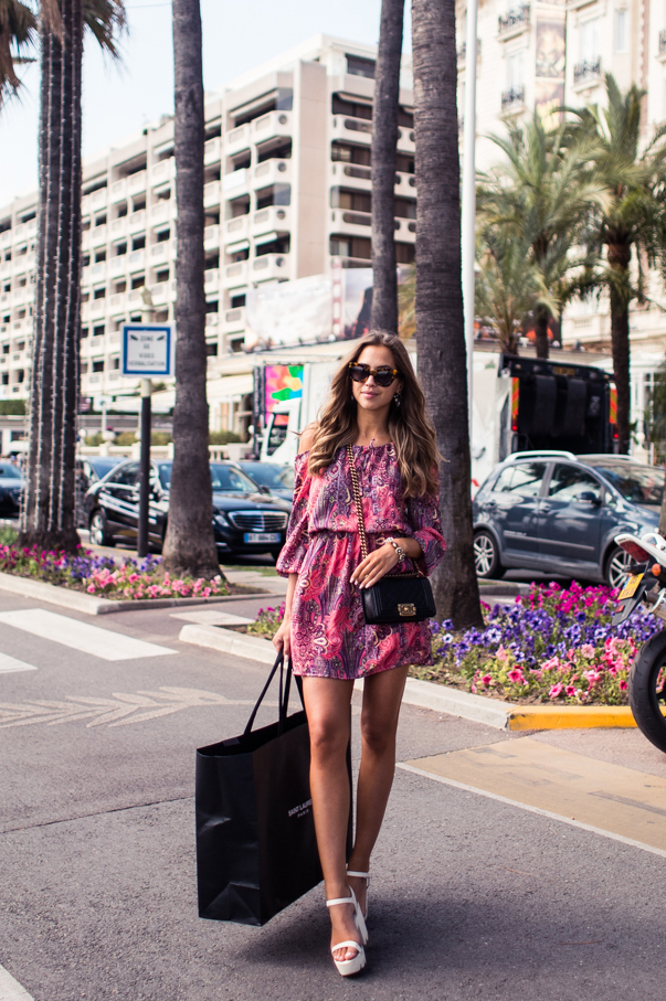 Kenza Zouiten in a boldly printed dress and white shoes  Dress: Nelly, Shoes: Jennie-Ellen, Sunglasses: Karen Walker
