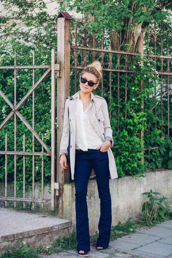 Katarzyna Tusk in dark blue flare jeans from River Island perfectly matched with a white skirt from Mango and the casual trench coat is from Zara