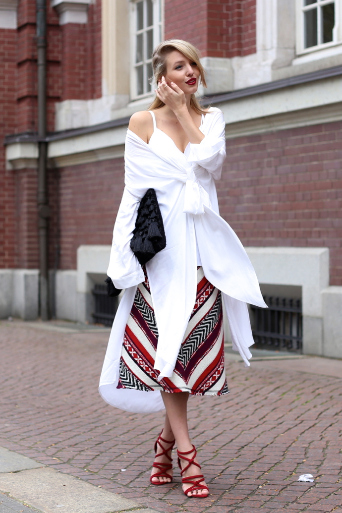 Leonie Sophie is wearing a H&M white bow blouse with a draped top, red heels and printed red and white skirt all from Zara