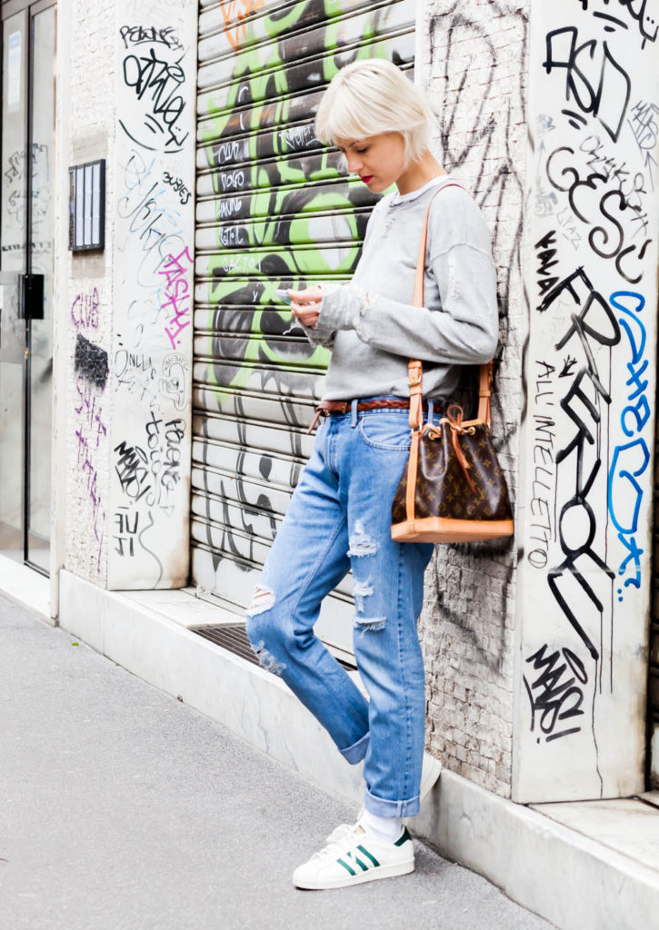 Street Style Fashion For May 2015: Linda Tol is wearing a grey distressed Mother sweater, light wash Redone denim jeans, white Adidas sneakers and a Louis Vuitton bucket bag
