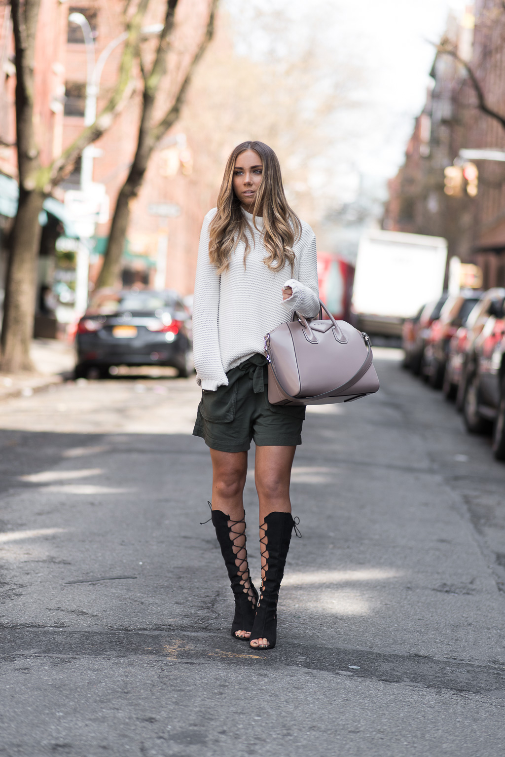 Just The Design: Lisa Olsson is wearing a pair of khaki green Gina Tricot shorts paired with a white Bascoto sweater, a Givenchy handbag and black lace up Nelly heels