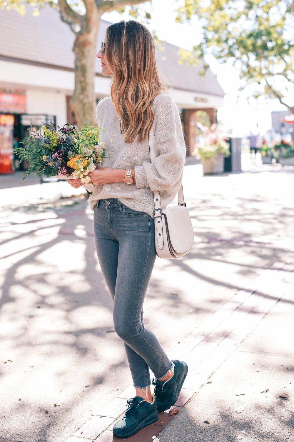 Sneakers are a must with skinny jeans and a sweater. Jess Ann Kirby has  chosen