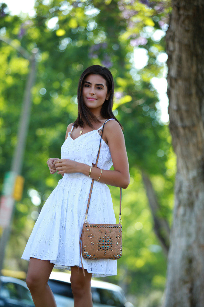 Sazan Barzani in a simply cute white dress outfit with an embellished bag  Dress: Nordstrom, Bag: Rebecca Minkoff
