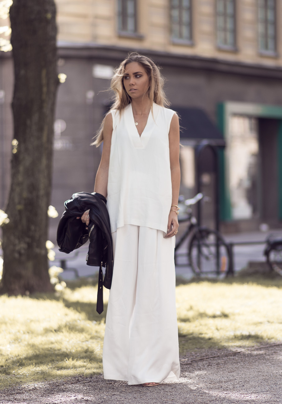 A simple white V-neck sleeveless top with white wide leg pants are set to be one of the classic spring outfits this year. Via Lisa Olsson Top/Pants: Gina Tricot