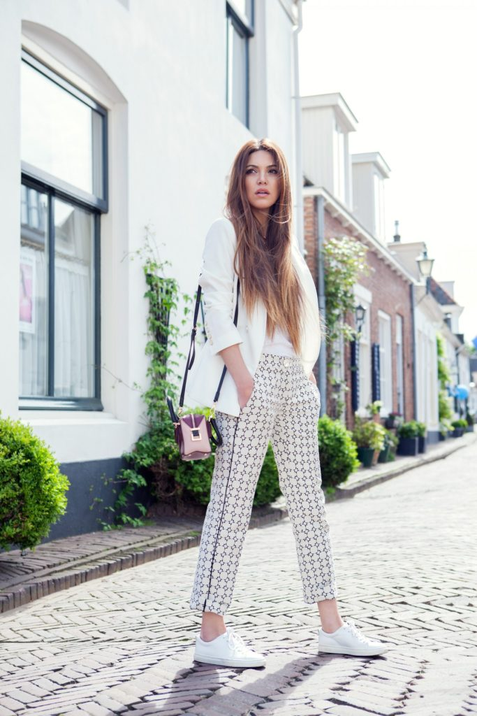 A light blazer, T-shirt and printed trousers combined with plain white sneakers. Via Negin Mirsalehi   Trousers: Via Delle Perle