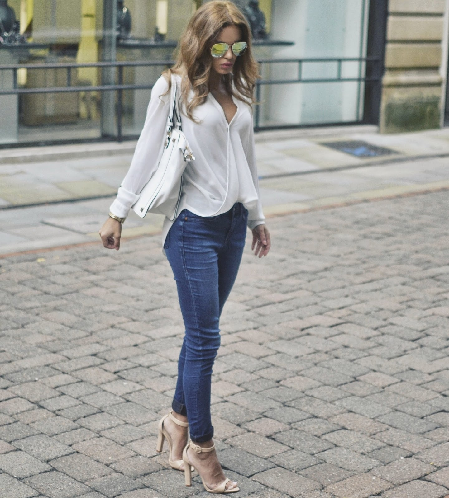 Nada Adelle wears denim skinny jeans and cute white wrap blouse. Top: River Island, Jeans: Topshop, Heels: Zara.