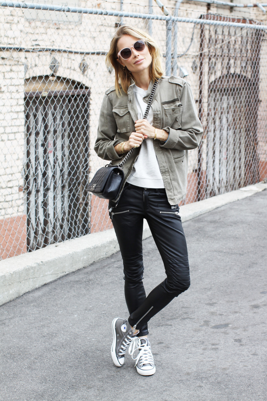 Anine Bing is wearing black leather trousers, military style army jacket, bag from Chanel, top from Sincere Jules and the shoes are from Converse